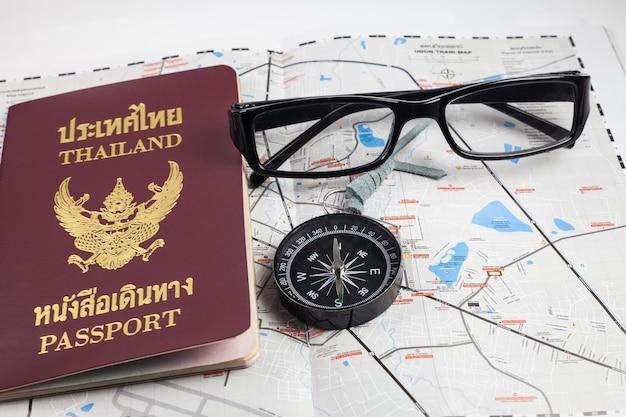 Bussola, passaporto, occhiali sulla mappa per i turisti