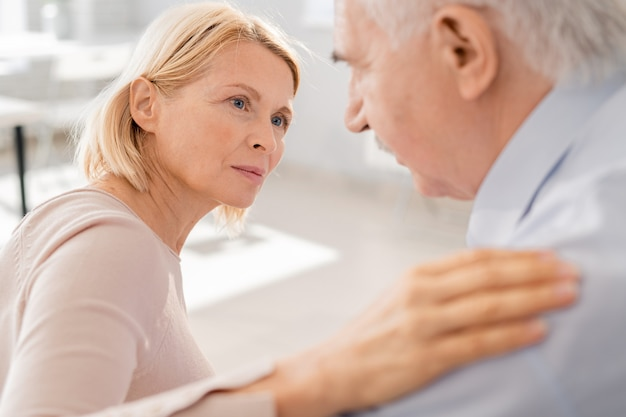 Femmina bionda invecchiata compassionevole che esamina l'uomo anziano di sofferenza mentre tiene la sua mano sulla sua spalla