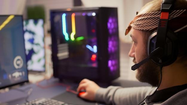 Giocatore professionista cyber competitivo in streaming con microfono, giocando a videogiochi sparatutto in prima persona durante il torneo virtuale. giocatore che utilizza il desktop del sistema rgb professionale in uno studio domestico di gioco fino a tardi