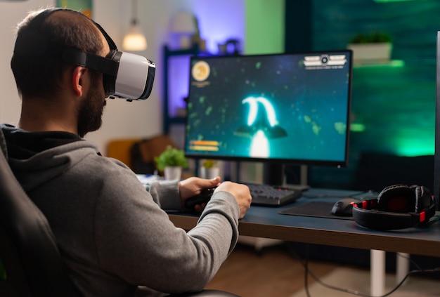 Giocatore competitivo che gioca al campionato di e-sport utilizzando la tecnologia wireless di rete uomo professionista che indossa l'auricolare vr e gioca a una competizione di sparatutto spaziale online su un computer potente