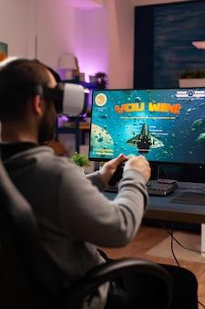 Giocatore competitivo che utilizza un joystick professionale che gioca a sparatutto online a tarda notte con auricolare vr. cyber streaming online virtuale che si esibisce durante il torneo di gioco dal vivo