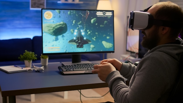 Campionato competitivo di videogiochi sparatutto spaziale vincente che indossa occhiali per realtà virtuale. pro cyber professionista che gioca con il joypad durante il torneo online utilizzando la tecnologia wireless di rete technology
