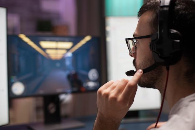 Giovane competitivo che gioca ai videogiochi sparatutto indossando le cuffie in una stanza con luce al neon.