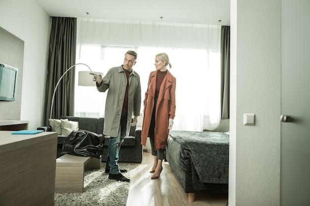 Ricerca completa. coppia di ricercatori professionisti che ispezionano la camera da letto lavorando in collaborazione