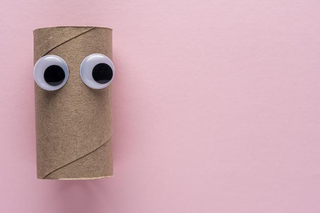Rotolo di carta igienica completato con occhi finti su sfondo rosa.