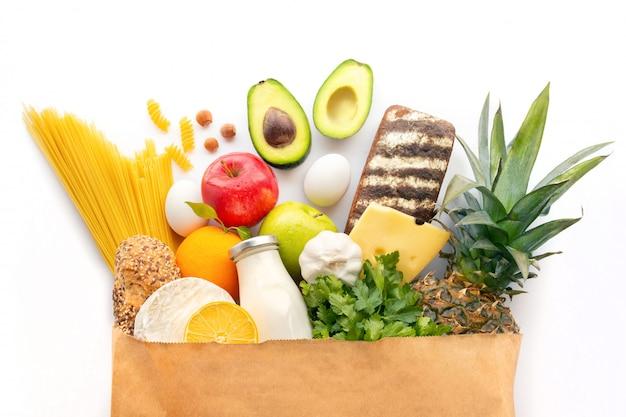 Un sacchetto completamente di carta con vari prodotti sani. sfondo di cibo sano. concetto di cibo di supermercato. latte, formaggio, frutta, verdura, avocado e spaghetti. shopping al supermercato. ingredienti.