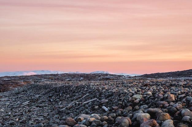 Terreno geologico complesso. incredibile paesaggio polare alba con una cresta di neve bianca di montagne dietro le montagne rocciose e una scogliera. teriberka.