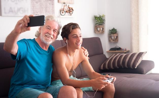 Complicità tra maschio adolescente e suo nonno. l'adolescente di 16 anni gioca ai videogiochi e l'uomo anziano usa il cellulare per un selfie. amore ed emozione. seduto al coperto su un divano marrone