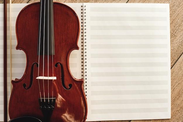 Composizione per violino. vista dall'alto del bellissimo violino marrone sdraiato su fogli per note musicali. lezioni di violino. strumenti musicali. apparecchiature musicali.