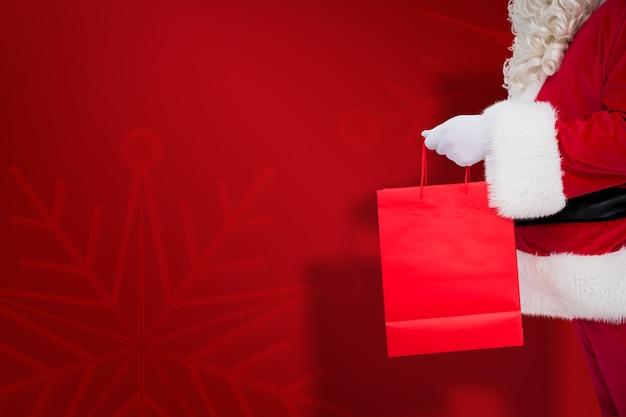 Immagine composita di babbo babbo natale con in mano una borsa della spesa