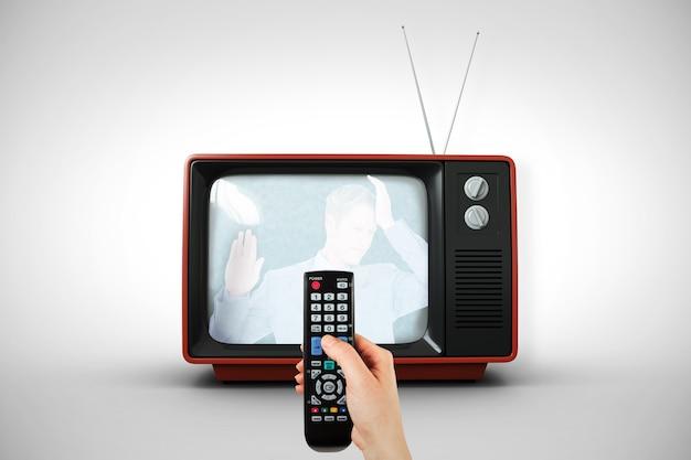 Immagine composita della mano che tiene il telecomando