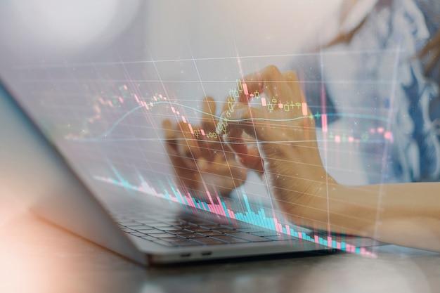 Una foto composita della mano di una donna che aziona un pc notebook e un grafico azionario