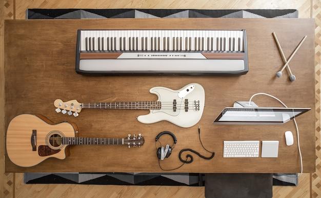 Composizione di chitarra acustica, basso elettrico, tasti musicali, cuffie, mixer audio e computer su un tavolo marrone in uno studio musicale.