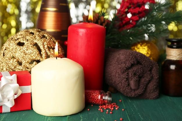 Composizione di candele accese, asciugamano e olio aromatico su un tavolo di legno verde su sfondo scintillante