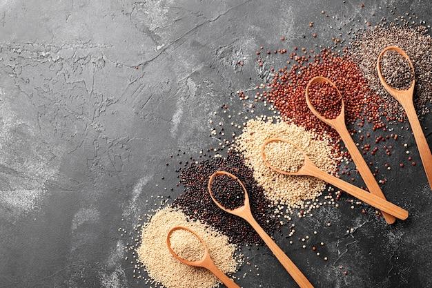 Composizione di amaranto, quinoa, chia in cucchiai di legno su fondo nero