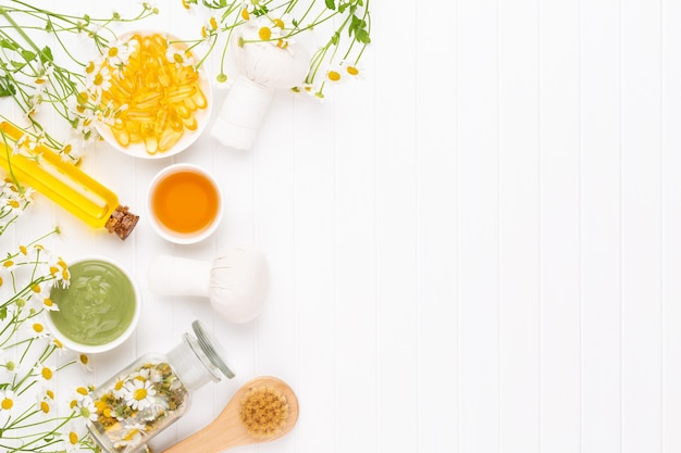 Composizione aromaterapia con cosmetici naturali e fiori di camomilla su sfondo chiaro.