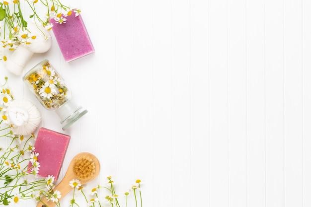 Composizione aromaterapia con cosmetici naturali e fiori di camomilla su sfondo chiaro