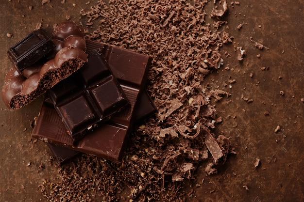 Composizione di barre e pezzi di latte diverso e cioccolato fondente, cacao grattugiato su una vista dall'alto di sfondo marrone da vicino