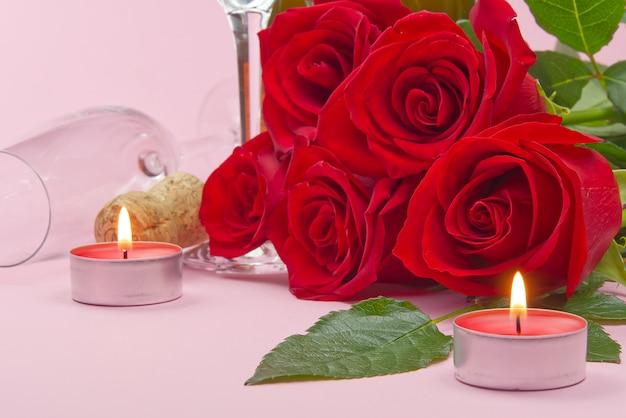 Una composizione di un bellissimo bouquet di rose, candele, bicchieri e una bottiglia di champagne crea una carta romantica. il concetto di san valentino, festa della mamma, 8 marzo.