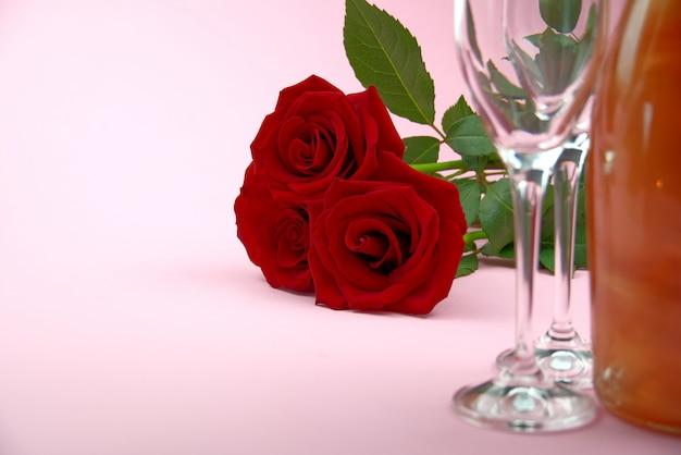 Una composizione di un bellissimo bouquet di rose, bicchieri e una bottiglia di champagne crea una romantica carta o poster. il concetto di san valentino, festa della mamma, 8 marzo.