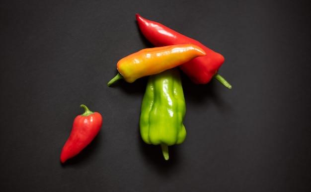 Composizione di peperoni di colore diverso su fondo nero scuro