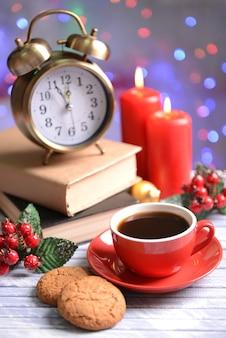 Composizione del libro con una tazza di caffè e decorazioni natalizie sul tavolo su sfondo luminoso
