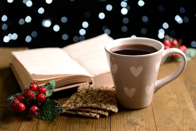 Composizione del libro con una tazza di caffè e decorazioni natalizie sul tavolo su sfondo scuro dark