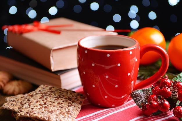 Composizione del libro con una tazza di caffè e decorazioni natalizie sul tavolo su parete scura dark