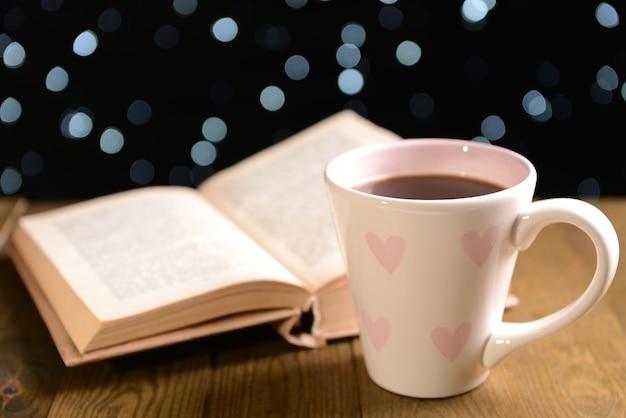 Composizione del libro con una tazza di caffè sul tavolo su sfondo scuro
