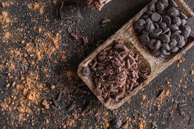 Composizione di gocce e scaglie di pezzi di cioccolato sfondo con diversi tipi di cioccolato