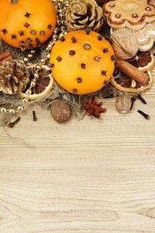 Composizione di spezie e mandarini natalizi, su fondo in legno