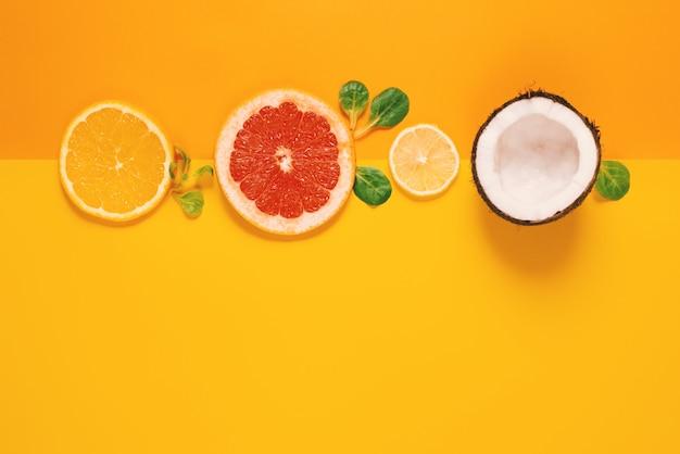 Composizione di agrumi, arancia, limone e cocco su sfondo giallo