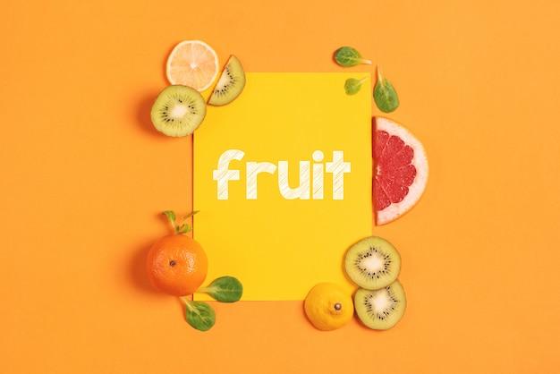 Composizione di agrumi, arancia, limone e kiwi su sfondo giallo