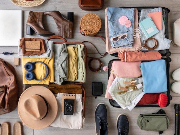 Composizione di vestiti e accessori in valigia
