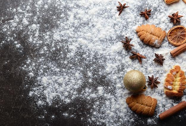 Composizione di biscotti, farina e decorazioni natalizie naturali sul tavolo grigio