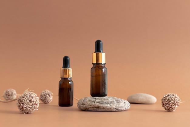 Composizione di flaconi cosmetici in vetro scuro con pipette con elementi naturali erba di pietra secca fiori di aglio sfondo garlic