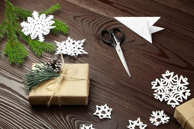 Composizione per tagliare i fiocchi di neve di carta sulla tavola di legno