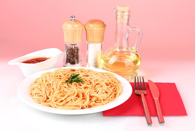 Composizione di deliziosi spaghetti cotti con salsa di pomodoro su colori brillanti