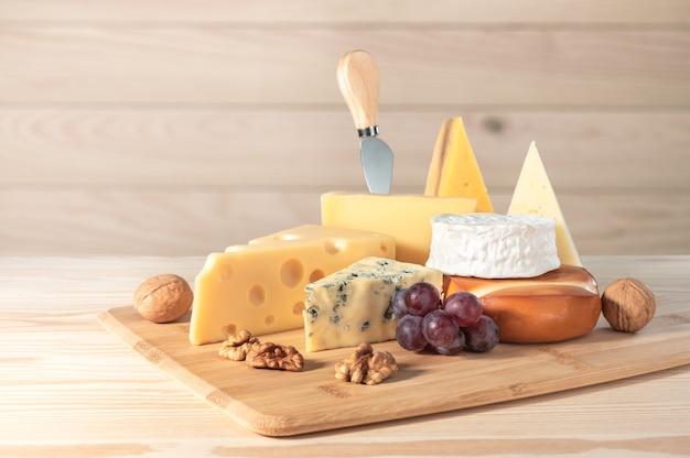 Composizione di diversi tipi di formaggio con noci e uva su fondo in legno. formaggio blu