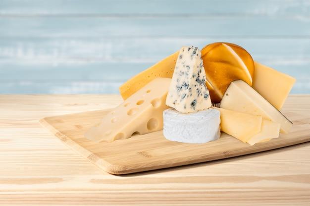 Composizione di diversi tipi di formaggio su fondo in legno. gorgonzola dorblu, suluguni affumicato, brie, maasdam, cheddar, parmigiano