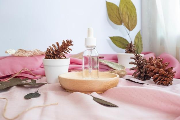La composizione mostra il prodotto. bottiglia trasparente per la cura della pelle con sfondo di foglie secche naturali. composizione minimalista con prodotti