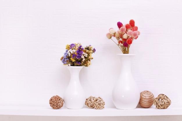 Composizione di fiori secchi sullo spazio muro bianco