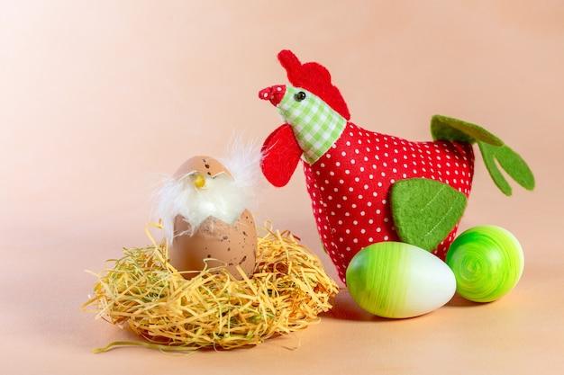 Composizione di uova di pasqua, pollo tessile e pollo nel nido