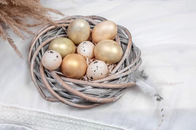 Composizione di uova in un nido e piume su sfondo chiaro.
