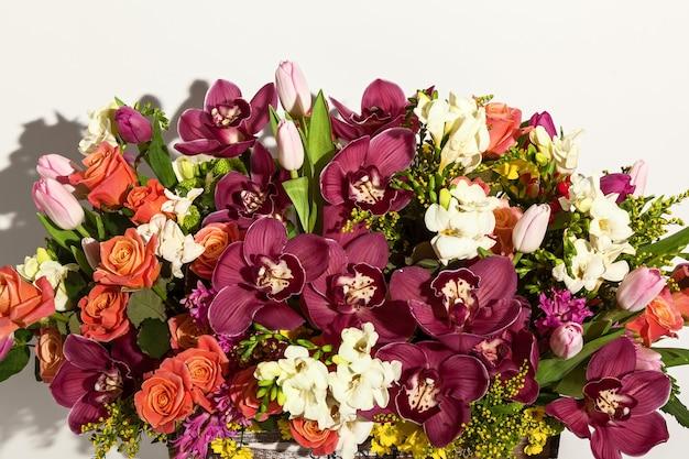 Composizione di fiori di rose rosa orchidee bordeaux tulipani rossi giacinto e hrzemtem