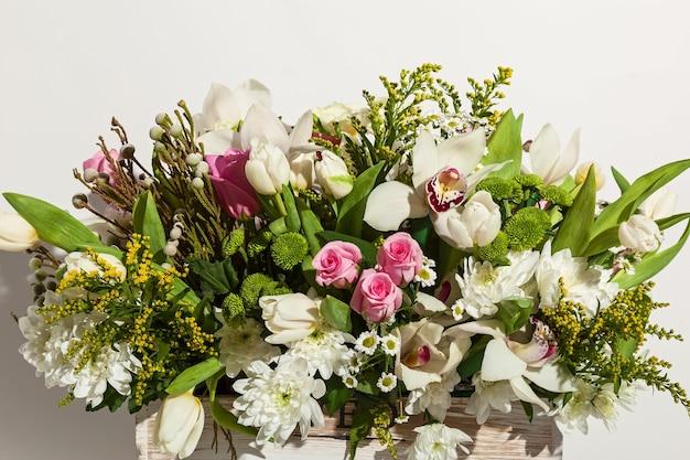 Composizione di fiori di rose rosa orchidee bianche tulipani rossi giacinto e hrzemtem