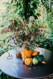 Composizione di fiori e zucche su un tavolo nero.