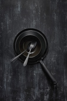 Composizione da attrezzature da cucina nere vuote per cucinare e preparare cibi naturali freschi e sani sullo stesso sfondo di pietra di colore. vista dall'alto.
