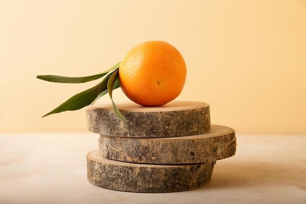 Composizione dal mandarino fresco con foglia verde sul podio dalle fette di legno naturale
