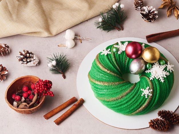 Composizione della torta di natale verde con coni e cannella